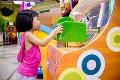 Menina chinesa pequena asiática que joga Arcade Game Machine Fotos de Stock Royalty Free