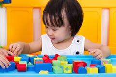 Menina chinesa pequena asiática que joga blocos de madeira Foto de Stock