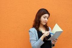 Menina chinesa que é livros de leitura Imagens de Stock