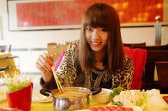 Menina chinesa que come o potenciômetro quente Foto de Stock