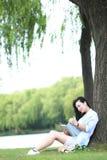 Menina chinesa que lê um livro sob a árvore A jovem mulher bonita loura com livro senta-se na grama Fotografia de Stock