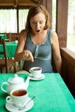 A menina chocada vê algo no copo do chá Imagem de Stock