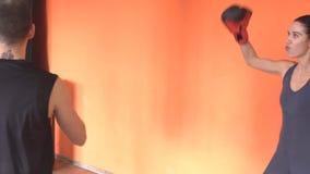 Menina coberta do pugilista que engana ao redor com o gym no exercício, instrutor, estilo de vida filme