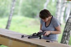 A menina cobra a pistola pneumática Fotos de Stock Royalty Free