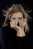 A menina cobre sua boca com um turtleneck preto fotos de stock
