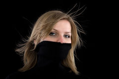 A menina cobre sua boca com um turtleneck preto fotografia de stock
