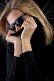 A menina cobre sua boca com um turtleneck preto foto de stock royalty free