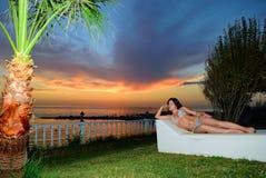 A menina coloca em uma cama da prancha no por do sol foto de stock royalty free