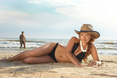 A menina coloca em uma praia em um chapéu Imagens de Stock Royalty Free