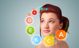 Menina com ícones coloridos da vitamina Fotografia de Stock Royalty Free