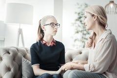 Menina com óculos pequena que senta-se e que comunica-se com a mãe fotografia de stock