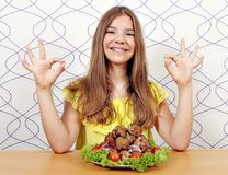 Menina com almôndegas e sinal aprovado da mão Fotografia de Stock