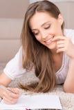 Menina com almofada de nota. Imagem de Stock
