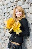 A menina com amarelo sae na parede de pedra do fundo Foto de Stock Royalty Free