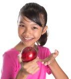 A menina com Apple e os polegares levantam o sinal II Imagens de Stock