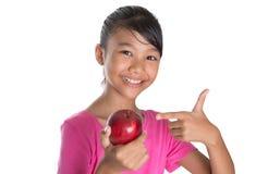 A menina com Apple e os polegares levantam o sinal III Foto de Stock Royalty Free