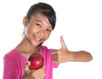 A menina com Apple e os polegares levantam o sinal IV Fotografia de Stock Royalty Free