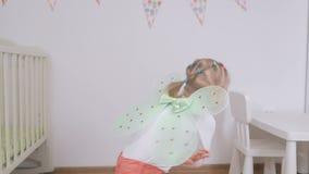Menina com as asas da borboleta do brinquedo que acenam seus braços atrás de sua dança traseira no berçário filme