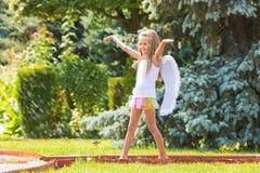 A menina com as asas do anjo no jardim aprecia espirra da água Fotografia de Stock Royalty Free