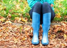 Menina com as botas de borracha azuis que sentam-se na terra Imagem de Stock