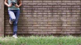 Menina com as calças de brim que inclinam-se contra a parede Imagem de Stock