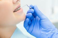 Menina com as cintas na recepção no close-up do dentista Mão com o instrumento nos dentes pacientes do ` s Imagens de Stock Royalty Free
