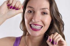 Menina com as cintas que limpam os dentes Fotografia de Stock