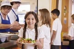 Menina com as dobras que guardam a placa do alimento no bar de escola Imagens de Stock