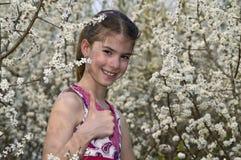 Menina com as flores brancas que mostram ESTÁ BEM o riso Fotografia de Stock