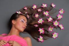 Menina com as flores cor-de-rosa em seu cabelo imagem de stock royalty free