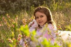 Menina com as flores da mola na natureza Imagens de Stock