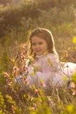 Menina com as flores da mola na natureza Imagens de Stock Royalty Free
