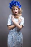 Menina com as flores em sua cabeça em um vestido no estilo do russo fotografia de stock royalty free