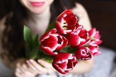 Menina com as flores vermelhas e brancas, tulipas Fotografia de Stock Royalty Free