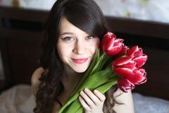 Menina com as flores vermelhas na cama Imagens de Stock