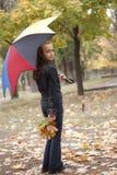 Menina com as folhas do guarda-chuva e do amarelo fotos de stock royalty free