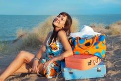 Menina com as malas de viagem no mar Foto de Stock Royalty Free