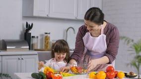 Menina com as necessidades especiais que ajudam a mamã que prepara a salada vídeos de arquivo