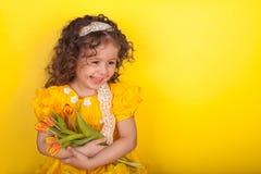 Menina com as tulipas nas m?os no fundo amarelo fotografia de stock royalty free