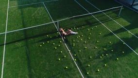 Menina com assentos do equipamento de esporte em um campo de tênis video estoque
