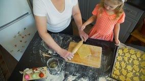 Menina com a avó que desenrola uma massa vídeos de arquivo