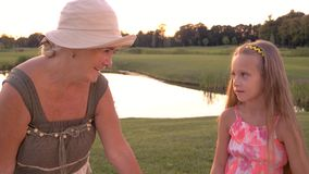 Menina com a avó que tem a conversação fora video estoque