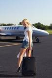 A menina com a bagagem que vai aplanar Fotografia de Stock Royalty Free