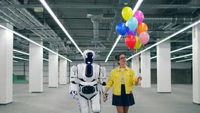 A menina com balões está andando com um robô alto vídeos de arquivo