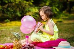 A menina com balões está bebendo a limonada em um piquenique Imagens de Stock