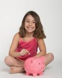 Menina com banco piggy Fotos de Stock Royalty Free