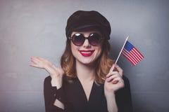 Menina com a bandeira dos EUA no fundo cinzento Fotografia de Stock