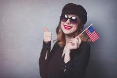 Menina com a bandeira dos EUA no fundo cinzento Imagem de Stock