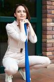 A menina com bastão de beisebol senta-se na porta fechado da loja e dos protetores ele Foto de Stock