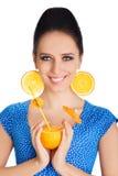 Menina com bebida alaranjada e fundo alaranjado do branco dos brincos da fatia Foto de Stock Royalty Free